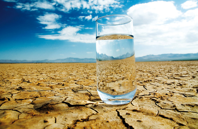 Glass of water in desert